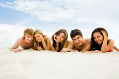 On the beach. Row of cheerful friends lying on sandy beach and smiling at camera Royalty Free Stock Image