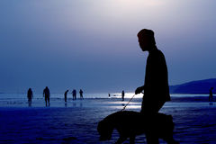 The beach. A man walking on the beach with a dog stock photo