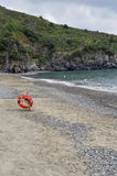 Beach. Lifebuoy with rope on the shoreline at the seaside Stock Images