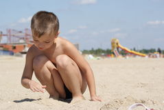 On a beach. Young boy 6 years old sits on seacoast and playing Stock Photo