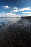 The beach. Wide angle view of a deserted beach - lighthouse in a distance Royalty Free Stock Images