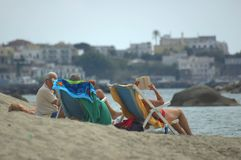 On the beach. People relaxing on the beach. Iscia-Town on background stock photo