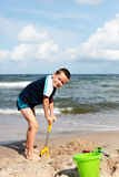 On the beach. 7 years old boy digging in the sand - kids stock images