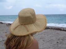 On the Beach. Girl with hat sitting on beach stock photos