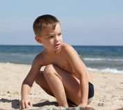 On a beach. Young boy 6 years old sits on seacoast and playing Royalty Free Stock Photography