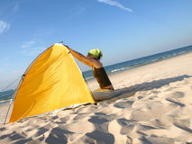 On the beach. Young woman sitting at colorful beach tent royalty free stock photo