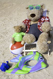 At the Beach. Oversized teddy bear dressed in Hawaiian shirt and shorts relaxing on the beach Stock Photography