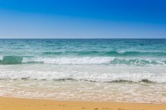 Seashore with flow. Vibrant beach shot with blue sky, turquoise sea flow and yellow sand stock photo