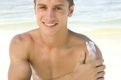 Beach. Attractive young man applying sunblock Royalty Free Stock Photo