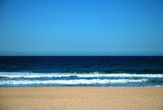 Beach. Sand, dark sea with waves reaching the beach, clear blue sky Royalty Free Stock Images
