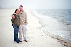 At the Beach. A young man and woman at the beach on a cold day stock image