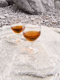 On a beach. Two wine-glasses with a drink on a sea beach in beams of the sun royalty free stock photo