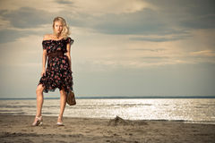 On the beach. A young pretty lady standing against the background of a seashore Royalty Free Stock Photos