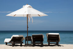 At the Beach. 3 chairs & an umbrella on the beach in Phuket, Thailand. Image is not sharpened for future editing. Copyspace can be extended by enlarging to the Royalty Free Stock Photo