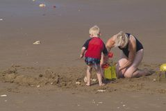 On the beach. Small male child making sandcastles on the beach with his Mom stock photography