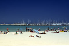 Beach. And people sunbathing with seawall and yachts in the background Royalty Free Stock Photography