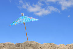 The Beach. A cocktail umbrella sits atop a sand dune on a lovely summer day Royalty Free Stock Photography