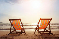 Beach. Two deckchairs on the beach with bright sun and waves Royalty Free Stock Photos