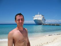 On the Beach. Young man on the beach at Grand Turk, British West Indies, with cruise ship at dock in background stock photography