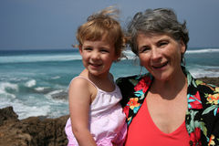 At the Beach. A grandmother and her granddaughter smile for the camera at the beach in Hawaii Stock Photography