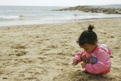On The Beach. A beautiful mixed race little girl playing on a sandy beach Stock Photography