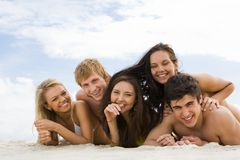 On the beach. Photo of cheerful friends lying on sandy beach and smiling at camera Stock Photos