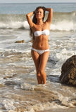 At the Beach. Beautiful young woman in white bikini posing at the beach Stock Photography
