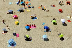 Beach from above. Beach seen from above, showing different colored sun shades and people at a distance Stock Photography