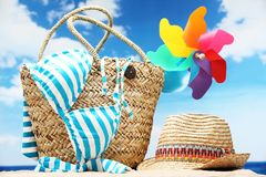 Beach accessories. Closeup of summer beach bag with items on sandy beach Stock Images