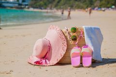 Beach accessories - bag, straw hat, sunglasses on white beach royalty free stock photo