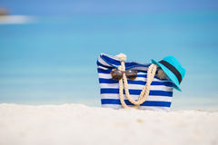 Beach accessories - blue bag, straw hat. Blue bag, straw hat, flip flops and towel on white beach Stock Photo
