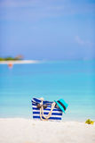 Beach accessories - blue bag, straw hat. Blue bag, straw hat, flip flops and towel on white beach Stock Image