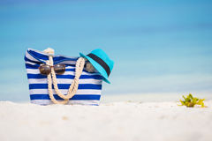 Beach accessories - blue bag, straw hat. Blue bag, straw hat, flip flops and towel on white beach Royalty Free Stock Photography