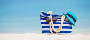 Beach accessories - blue bag, straw hat. Blue bag, straw hat, flip flops and towel on white beach Royalty Free Stock Images