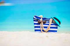 Beach accessories - blue bag, straw hat. Blue bag, straw hat, flip flops and towel on white beach Royalty Free Stock Photo