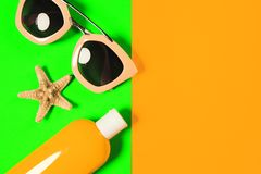 Beach accessories on a bright colorful background. Dried starfish, trendy pink sunglasses and a bottle of sunscreen lotion. Summer. Vacation background.Top view royalty free stock images