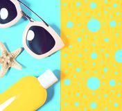 Beach accessories on a bright colorful background. Dried starfish, trendy pink sunglasses and a bottle of sunscreen lotion. Summer. Vacation background.Top view royalty free stock photo