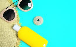 Beach accessories on a bright green colorful background. Trendy pink sunglasses, a bottle of sunscreen lotion, a fragment of a. Straw hat and sea urchin shell stock images