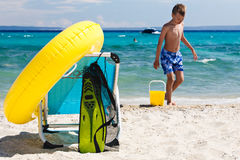 Beach accessories and chair on beach and child playing Royalty Free Stock Photography