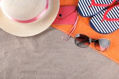 Beach accessories. Flip-flops, hat and glasses on an orange towel on the sea sand. Top view royalty free stock photo
