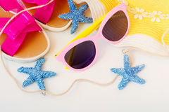 Beach accessories. Flip flops, hat and starfish on white background. Top view with copy space Stock Images