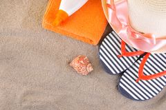 Beach accessories. Flip-flops, a hat and a sunscreen on an orange towel on the sea. Top view royalty free stock photo