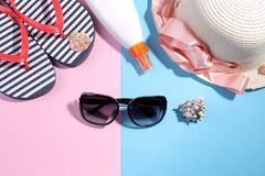 Beach accessories. Flip-flops and a summer hat with black sunglasses and cream on a bright pink and blue background. Top view stock image