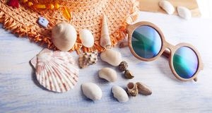 Beach accessories glasses hat cockleshells on wood deck. Beach accessories glasses hat cockleshells on wood deck Stock Image