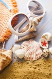 Beach accessories glasses hat cockleshells on wood deck. Beach accessories glasses hat cockleshells on wood deck stock images