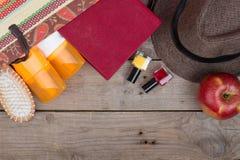 Hairbrush, orange towel, hat, sun cream, lotion, beach bag, nail polish, a book on a brown wooden background. Beach accessories - hairbrush, orange towel, hat stock photos