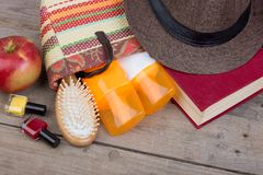 Beach accessories - hairbrush, orange towel, hat, sun cream, lotion, beach bag, nail polish, book on a brown wooden background. Beach accessories - hairbrush stock photos