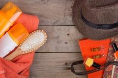 Beach accessories - hairbrush, orange towel, hat, sun cream, lotion, beach bag, nail polish, a book on brown wooden background. Beach accessories - hairbrush royalty free stock image