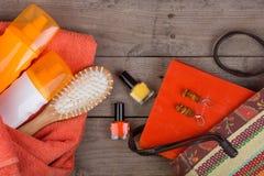 Beach accessories - hairbrush, orange towel, sun cream, lotion, beach bag, nail polish, a book on brown wooden background. Beach accessories - hairbrush, orange royalty free stock photo