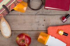 Beach accessories - hairbrush, orange towel, sun cream, lotion, beach bag, nail polish, a book on brown wooden background. Beach accessories - hairbrush, orange stock image